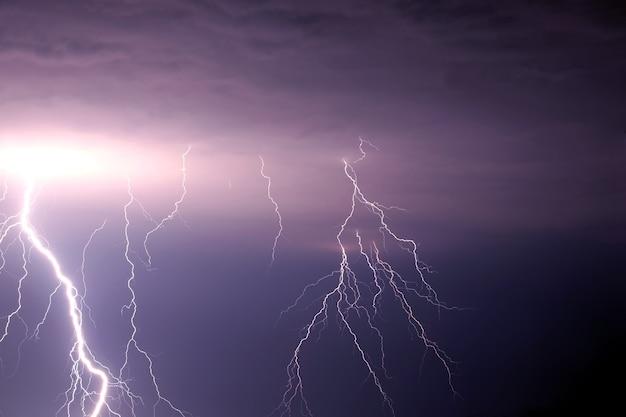 Viele helle blitze entladen sich am stürmischen himmel unter schweren lila regenwolken Premium Fotos