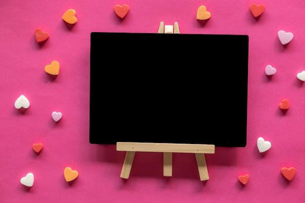 Viele herzen um tafel auf rosa hintergrund, liebesikone, valentinstag, beziehungskonzept Premium Fotos