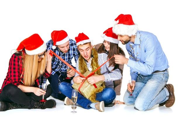 Viele junge frauen und männer, die an der weihnachtsfeier auf weißem studiohintergrund mit geschenk trinken Kostenlose Fotos