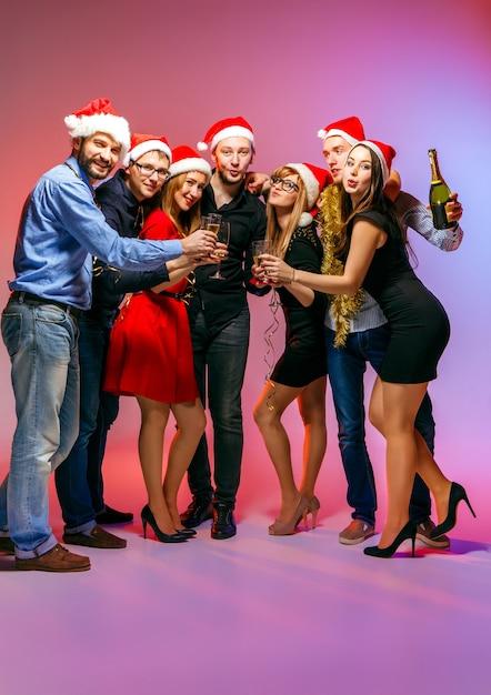 Viele junge frauen und männer trinken auf der weihnachtsfeier im rosa studio Kostenlose Fotos