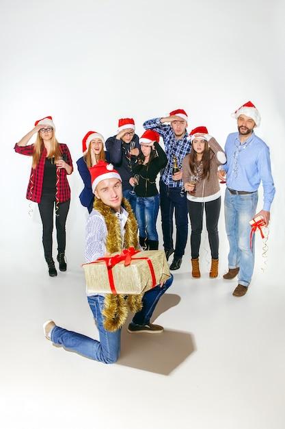 Viele junge frauen und männer trinken auf der weihnachtsfeier im weißen studio Kostenlose Fotos