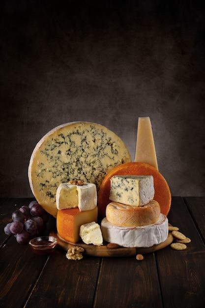 Viele käsesorten auf einem holzbrett mit nüssen und honig Premium Fotos