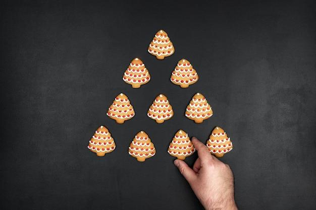 Viele kekse formten weihnachtsbaum auf einem schwarzen tafelhintergrund, minimalistisches neujahrskonzept mit einer hand Premium Fotos