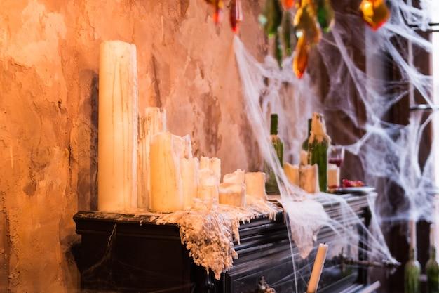 Viele kerzen stehen am klavier. unheimliches spinnennetz deckte flaschen mit kerzen und kandelabern in der geisterhauseinstellung ab. interieur und dekorationen für halloween-party. stillleben im spukhaus. Premium Fotos