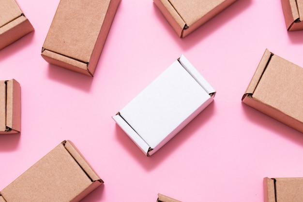 Viele kleine pappkartons auf rosa tisch Premium Fotos