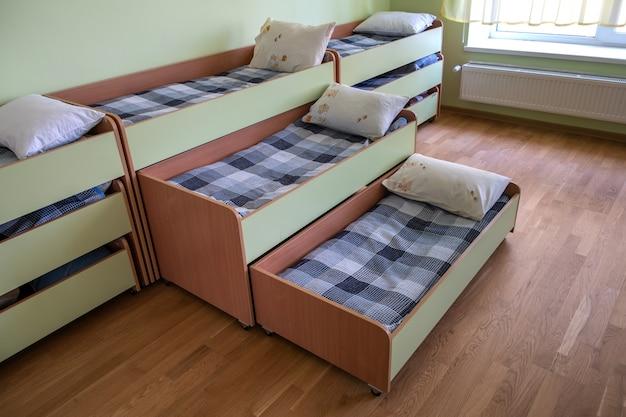 Viele kleinen betten im leeren schlafzimmer der kindertagesstättevorschule. Premium Fotos