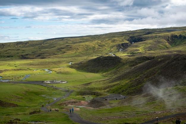 Viele menschen gehen auf einem schmalen pfad in einem grünen land, umgeben von grünen hügeln Kostenlose Fotos