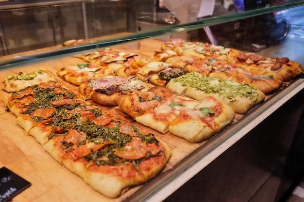 Viele mini-pizzen an der theke. verschiedene arten von pizzen sind sehr unterschiedlich Premium Fotos