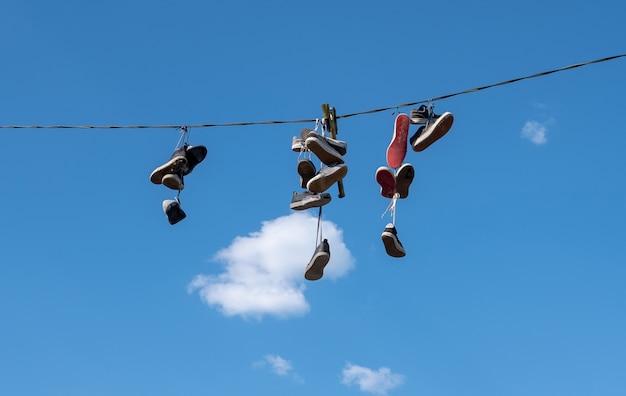 Viele paar sportschuhe hingen an einem seil vor blauem himmel. Premium Fotos
