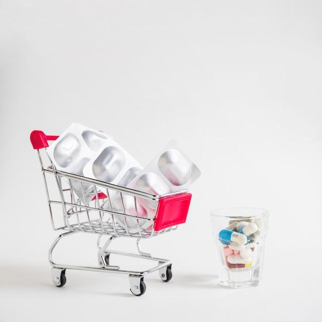 Viele pillen im kleinen glas mit einkaufswagen mit silbernen blisterpillen auf weißem hintergrund Kostenlose Fotos