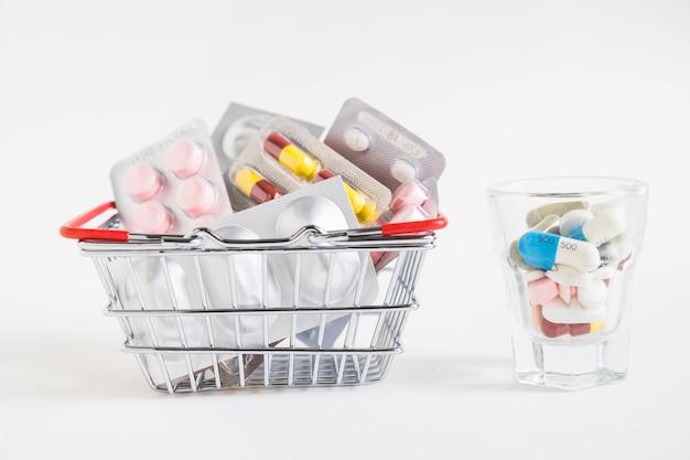 Viele pillen verpacken im einkaufswagen und im glas auf weißem hintergrund Kostenlose Fotos