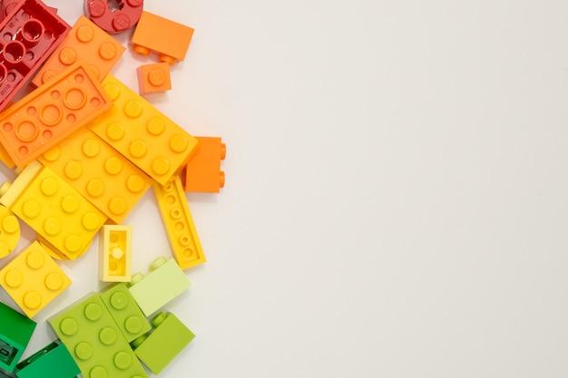 Viele plastikerbauerwürfel auf weißem hintergrund. beliebtes spielzeug. Premium Fotos