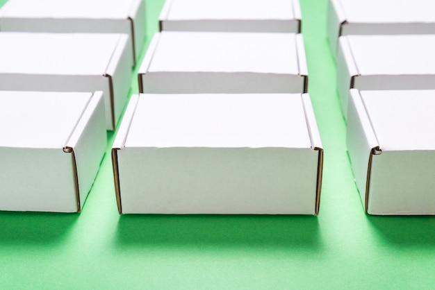 Viele quadratische kartonschachteln auf grünem hintergrund Premium Fotos
