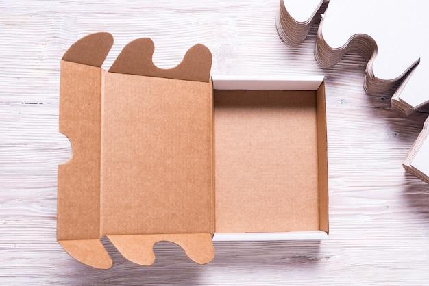 Viele quadratische kartonschachteln auf hölzernem hintergrund, geschnitten Premium Fotos