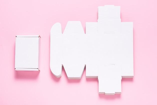 Viele quadratische kartonschachteln auf rosa hintergrund, geschnitten Premium Fotos