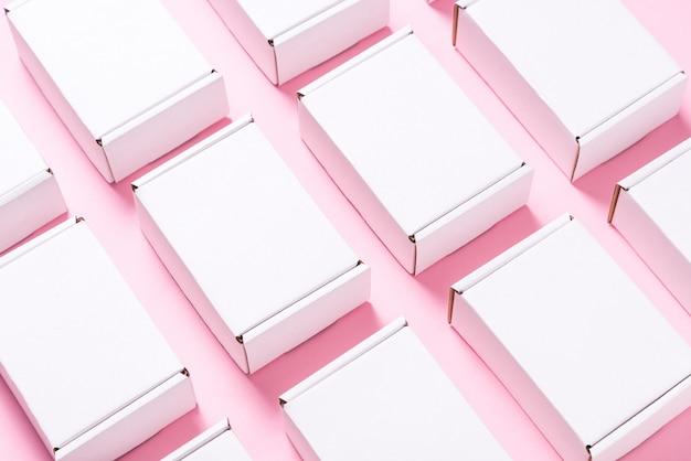 Viele quadratische kartonschachteln auf rosa hintergrund Premium Fotos