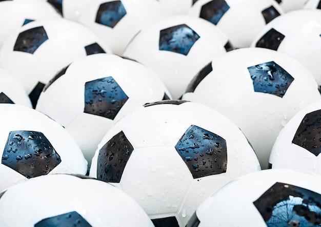 Viele schwarzweiss-fußbälle. fußballkugeln in einem wasser Premium Fotos