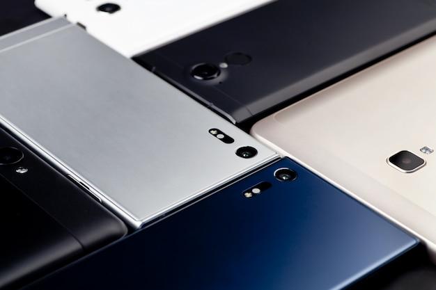 Viele smartphones und tablets liegen auf dem tisch. der blick von oben. Premium Fotos