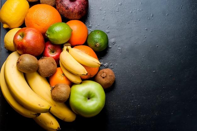 Viele verschiedene früchte auf schwarzem hintergrund Premium Fotos
