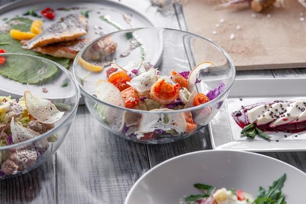 Viele verschiedene gerichte, fisch und salate werden am tisch im restaurant serviert. Premium Fotos