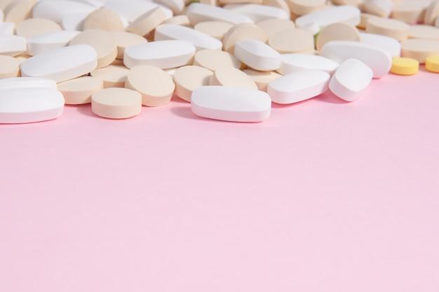 Viele verschiedene pillen auf einem rosa hintergrund Premium Fotos