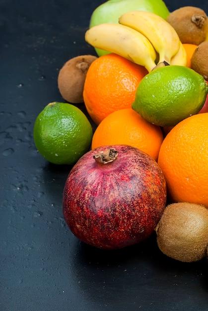 Viele verschiedenen früchte auf einem schwarzen hintergrund Premium Fotos