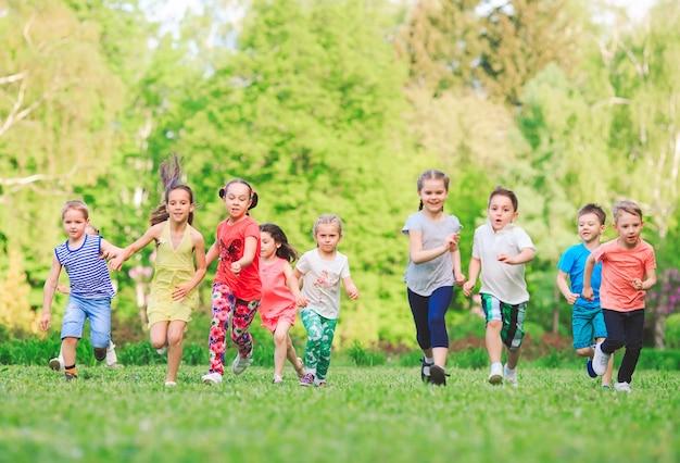 Viele verschiedenen kinder, jungen und mädchen, die in den park am sonnigen sommertag in der zufälligen kleidung laufen Premium Fotos