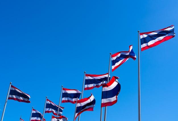 Viele von thailand flagge, die oben auf fahnenmast gegen blauen himmel weht Premium Fotos