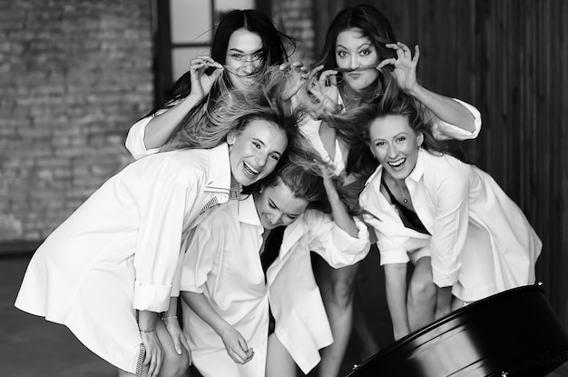 Vielfältige gruppe von freundinnen, die auf einer party genießen und lachen. gruppe schöne glückliche frauen, die spaß in der weißen kleidung haben. Premium Fotos