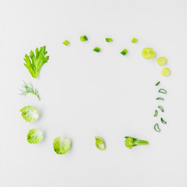 Vielzahl des grünen gemüses, das kreisrahmen auf weißem hintergrund bildet Kostenlose Fotos
