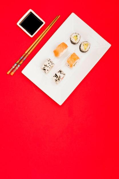 Vielzahl von asiatischen rollen vereinbarte auf weißem behälter nahe sojasoßenbad und -essstäbchen über rotem hintergrund Kostenlose Fotos