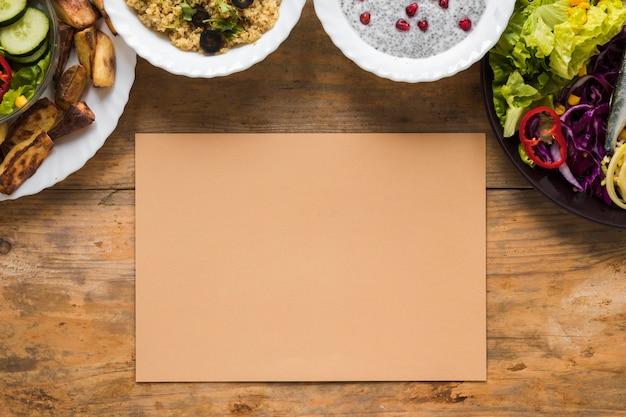 Vielzahl von gesunden nahrungsmitteln in der schüssel mit leerem braunem papier auf holztisch Kostenlose Fotos