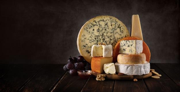 Vielzahl von käse auf einem hölzernen brett mit nüssen und honig Premium Fotos