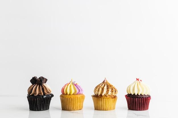 Vielzahl von kleinen kuchen auf weißem hintergrund Premium Fotos