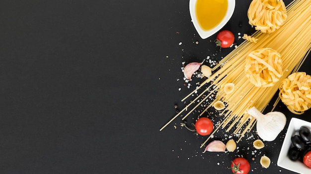 Vielzahl von rohen nudeln; kirschtomate; olivenöl; knoblauch und schwarze oliven auf schwarzem hintergrund Kostenlose Fotos