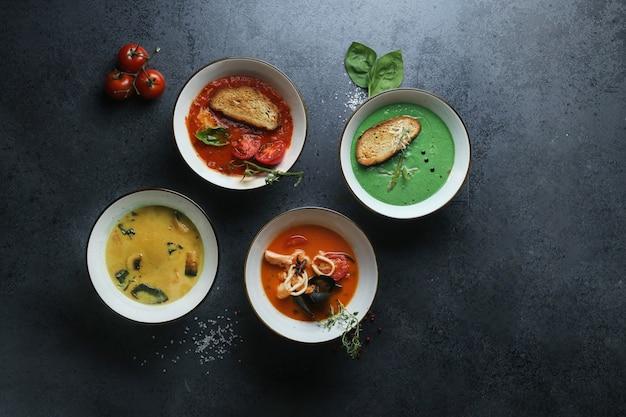 Vier arten von cremesuppen aus tomaten, pilzen, meeresfrüchten und basilikum Kostenlose Fotos