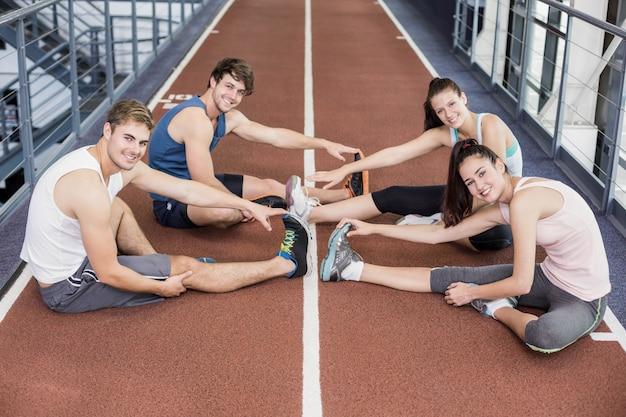 Vier athletische frauen und männer, die auf laufbahn ausdehnen Premium Fotos