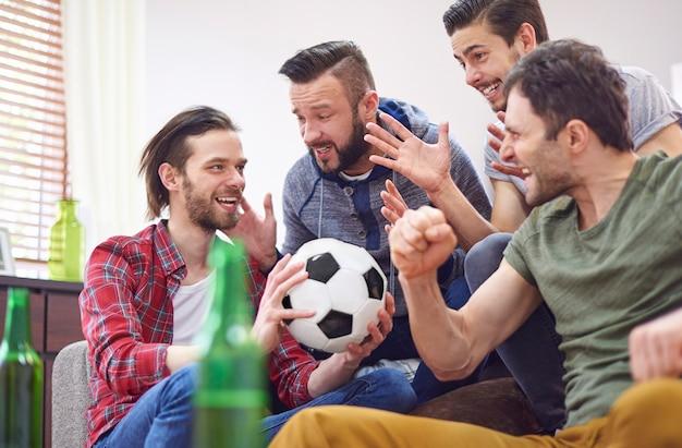 Vier beste freunde sprechen über fußballspiel Kostenlose Fotos