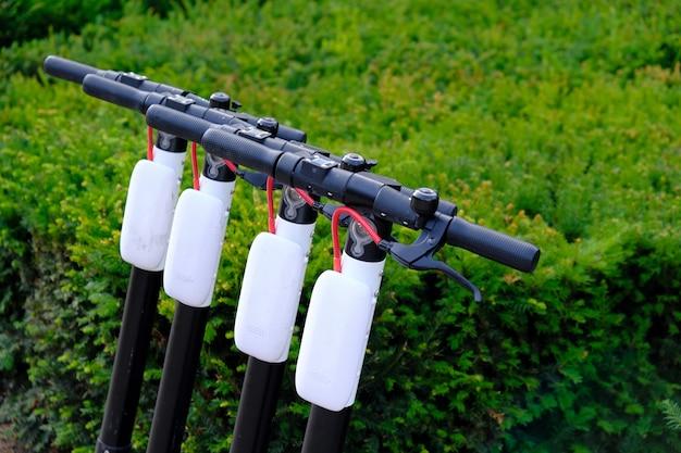 Vier elektroroller parkten in einer reihe auf dem bürgersteig der stadt. Premium Fotos