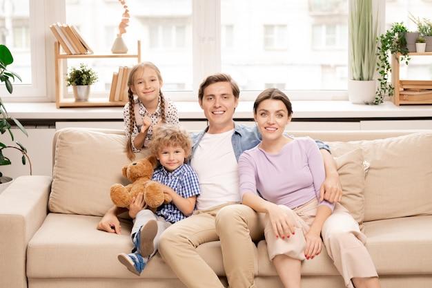 Vier familienmitglieder in freizeitkleidung sitzen auf der couch am fenster Premium Fotos