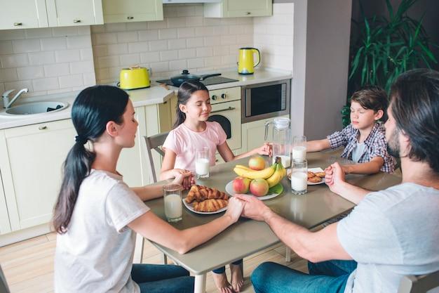 Vier familienmitglieder sitzen zusammen am tisch und halten sich an den händen. sie halten die augen geschlossen. die familie betet. Premium Fotos