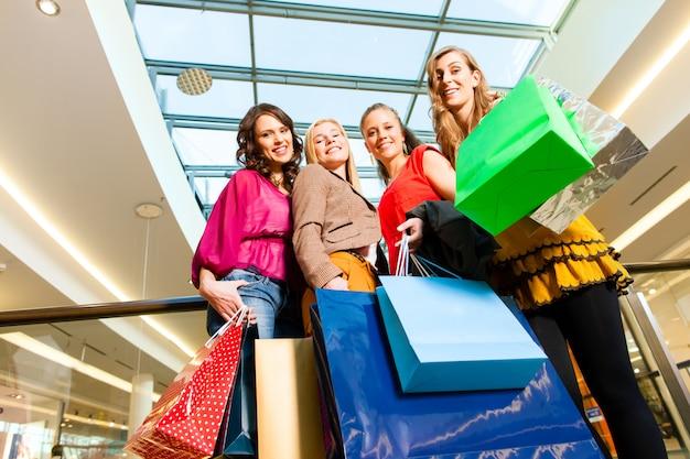 Vier freundinnen in einem einkaufszentrum einkaufen Premium Fotos