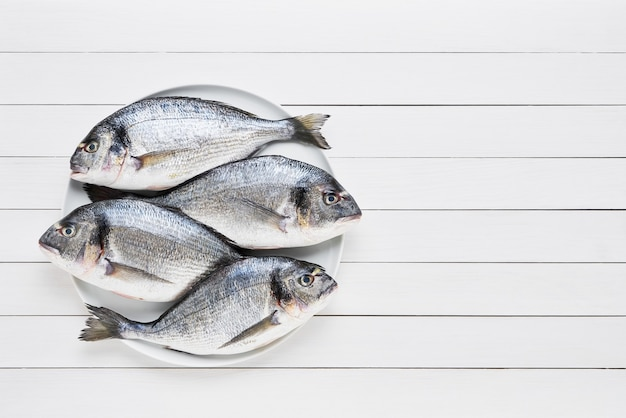 Vier frische brassenfische mit vergoldetem kopf auf einer schüssel auf einem weißen holztisch. gesundes lebensmittelkonzept. draufsicht Premium Fotos