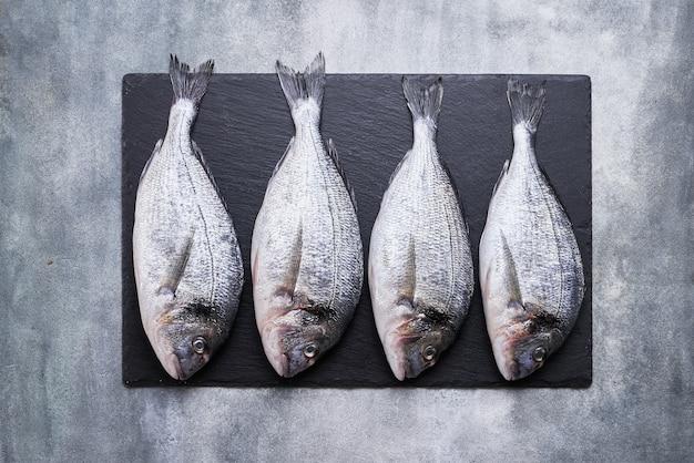 Vier frische königliche doraden auf grauem betonhintergrund. gesundes lebensmittelkonzept. draufsicht, kopierraum. mediterranes meeresfrüchte-konzept Premium Fotos