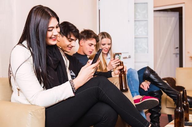 Vier glückliche freunde, die ihre handys benutzen, die zu hause auf einer couch sitzen - glückliche freunde, die zusammen sitzen, aber alle auf ihre smartphones schauen und bier trinken. Premium Fotos