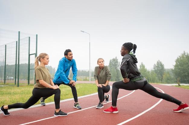 Vier junge freundliche aktive menschen in sportbekleidung, die auf rennstrecken im stadion in natürlicher umgebung trainieren Premium Fotos