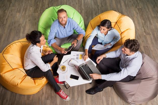 Vier junge kollegen auf beanbag stühle arbeiten Kostenlose Fotos