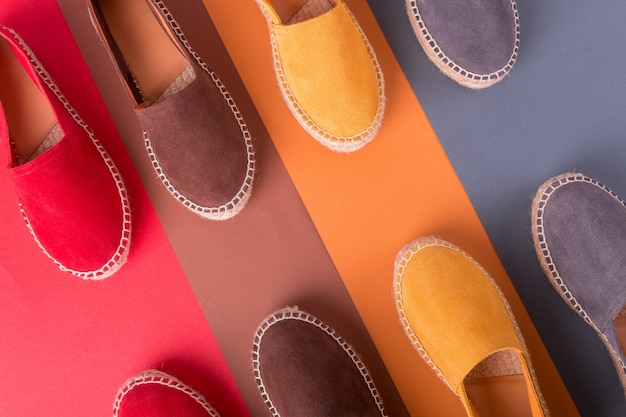 Vier paare espadrilles auf mehrfarbenhintergrund. ansicht von oben. Premium Fotos