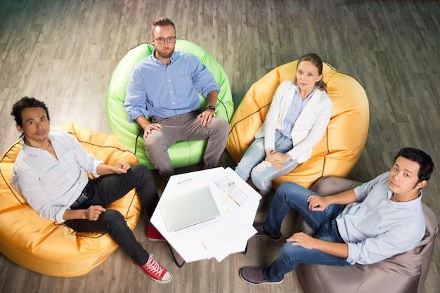 Vier personen sitzen auf sitzsack sessel um den tisch Kostenlose Fotos