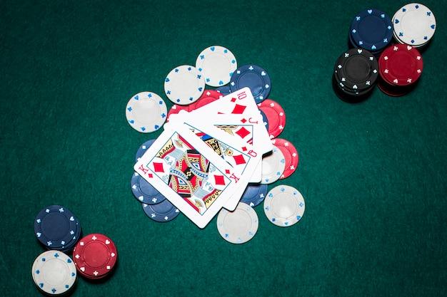 Vier spielkarten, die einen royal flush im diamanten über dem kasino zeigen, bricht auf grüner pokertabelle ab Kostenlose Fotos